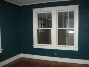 the master bedroom.  the window looks out on the addition/bonus room.  and who doesn't like dark teal walls?
